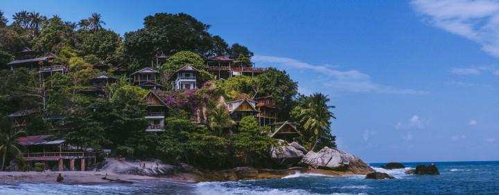 beachfront property, lush greenery, ocean, huts