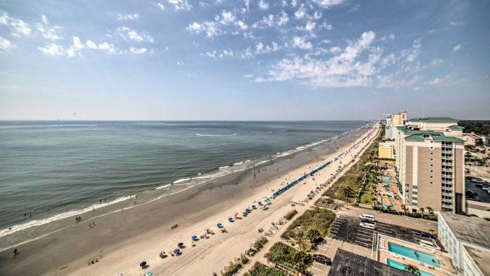 Hero_-_View_from_a_top_floor_looking_down_onto_the_beach_lined_with_beach_umbrellas_and_beach_ch ...